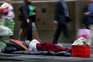 homeless man sleeping on footpath