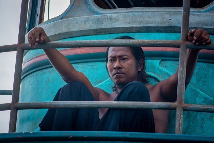 A man with serious expression sits with no shirt on worn-out fishing boat with fading blue paint, hands resting on boat railing.