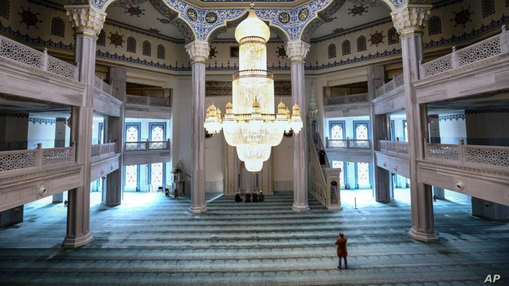 A believer and a group of mullahs attend a Friday prayer in the Moscow Cathedral Mosque in Moscow, Russia.