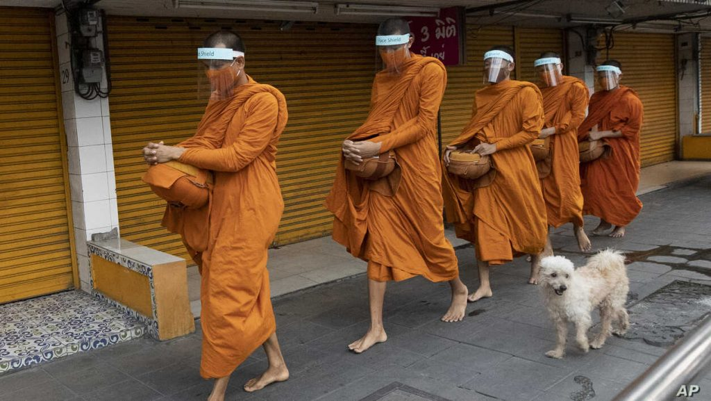 Buddhist monks wear face shields to protect themselves from new coronavirus as they walk to collect alms from devotees in Bangkok, Thailand.