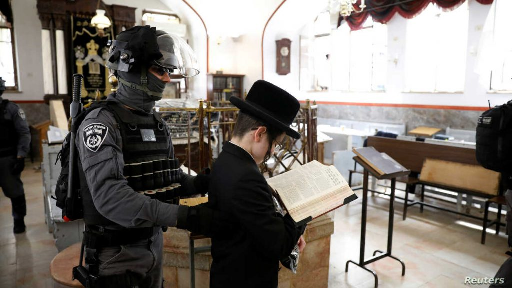 An Israeli policeman removes an ultra-Orthodox Jewish