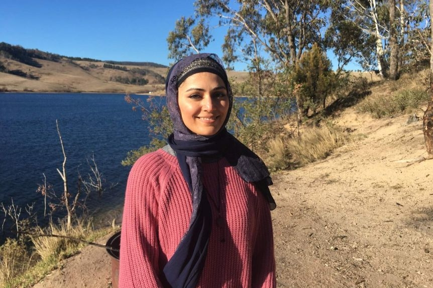 Mahsheed Ansari wearing hijab and standing in front of a lake.