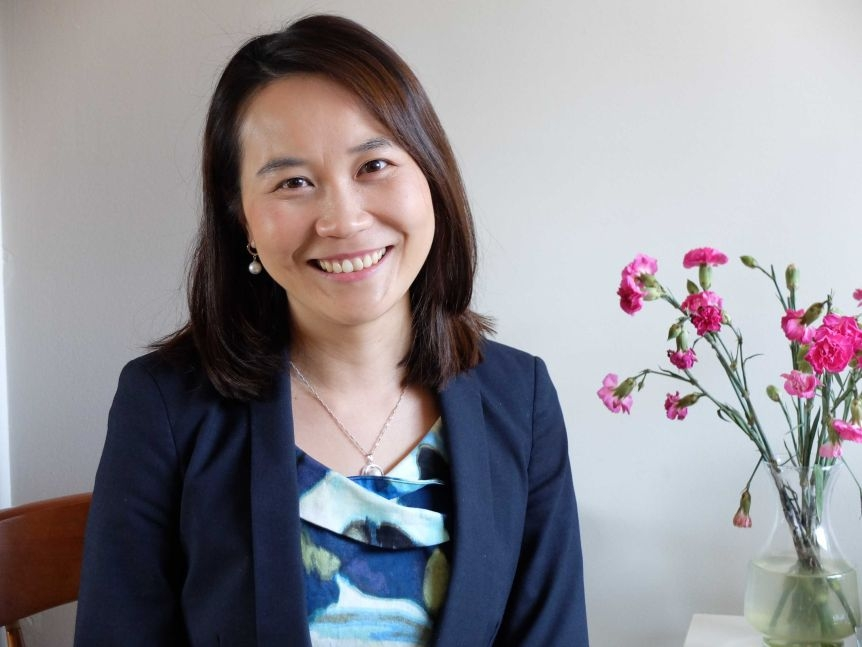 Lawyer Tina Ng in front of white wall, with flowers beside her.