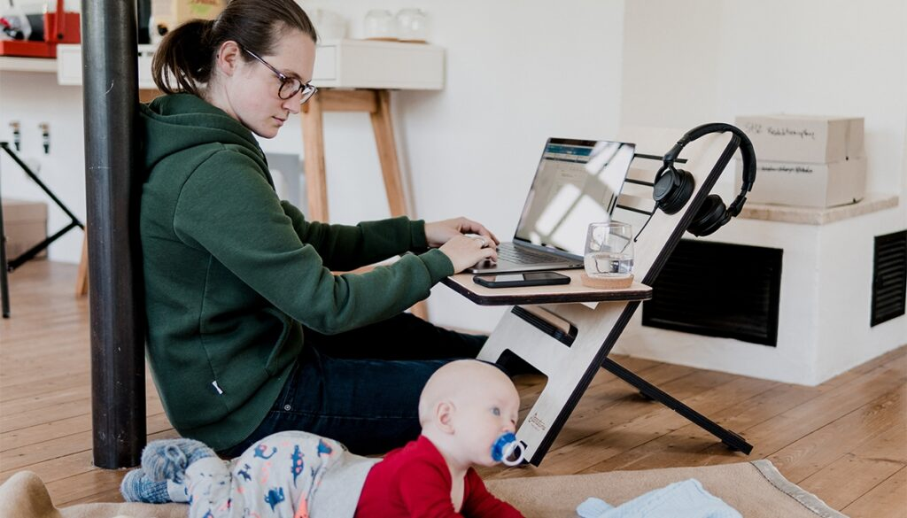 A mother looking at child while working