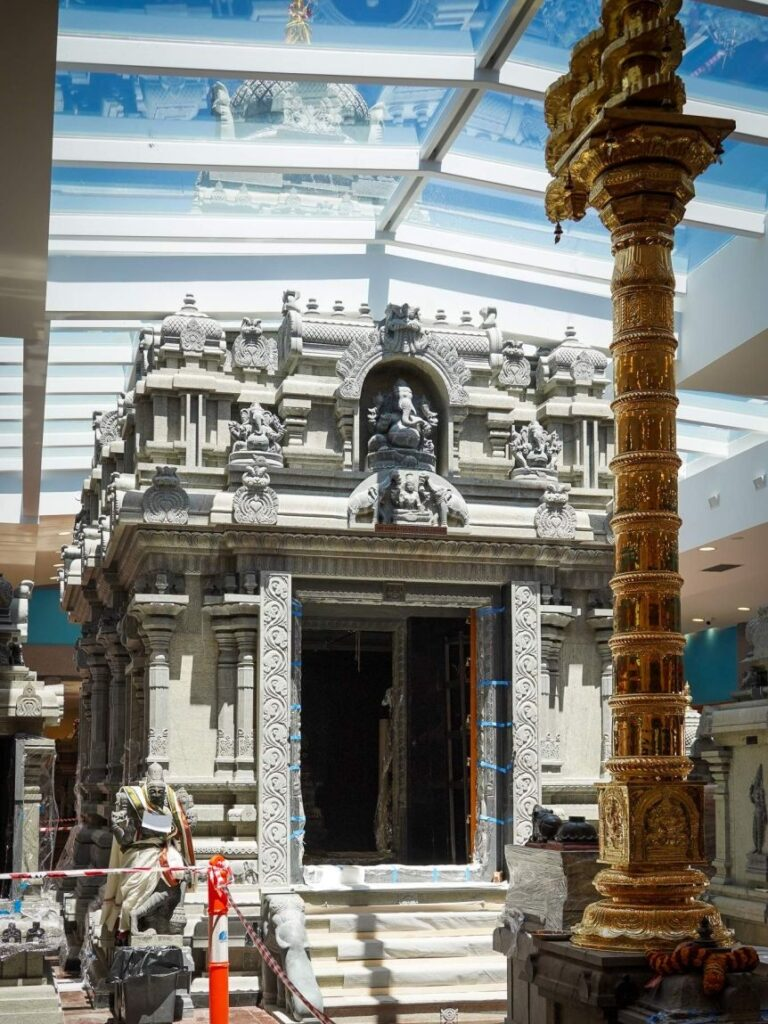 A decorative Hindu granite shrine sits inside a temple